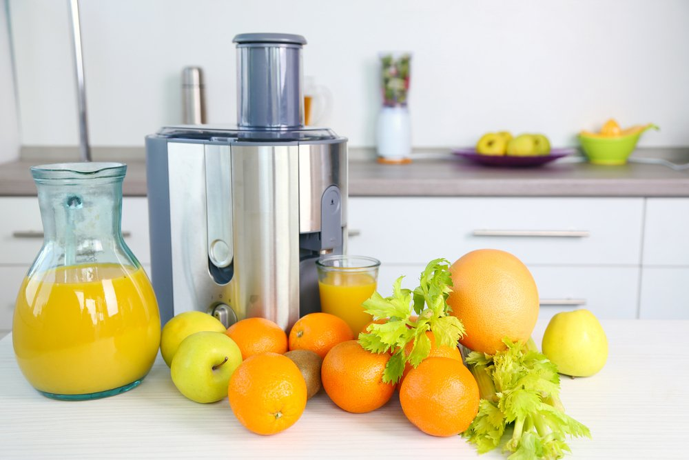 Oranges, Apples and greens next to juicer