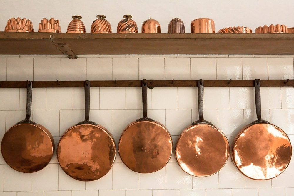 Copper pots and pans hanging on a wall